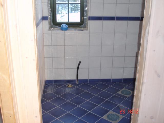 Flislagt gulv lagt diagonalt med sokkelflis og flislagte vegger - borde av gulvflis