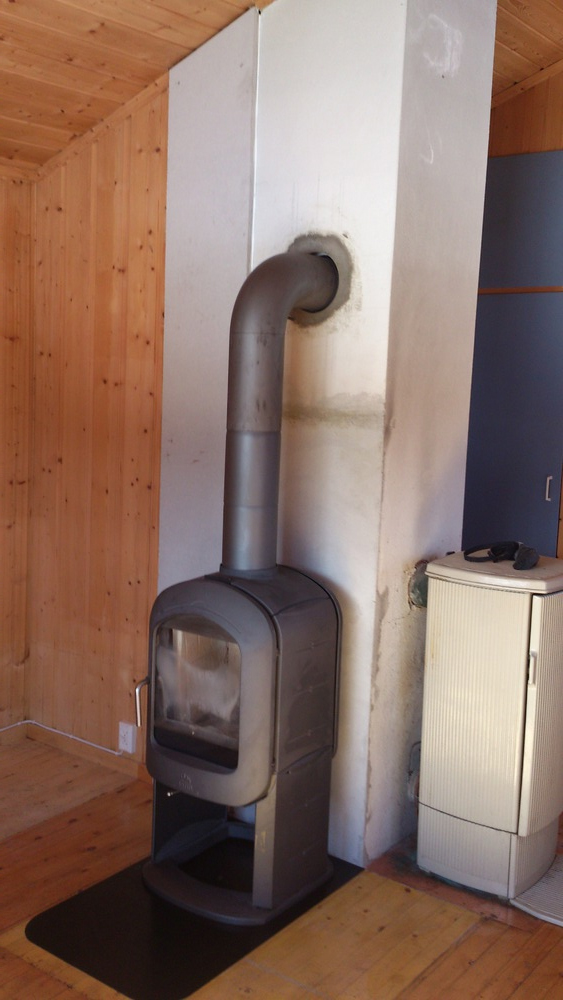 Rivd gammel peis, forblendet og reparert pipe, satt opp brannmursplate mot vegg og montert ovn. Skramstadsætra