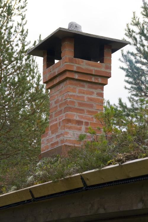 Teglstenspipe murt opp i tidsriktig stil i en restaurert tømmerkoie