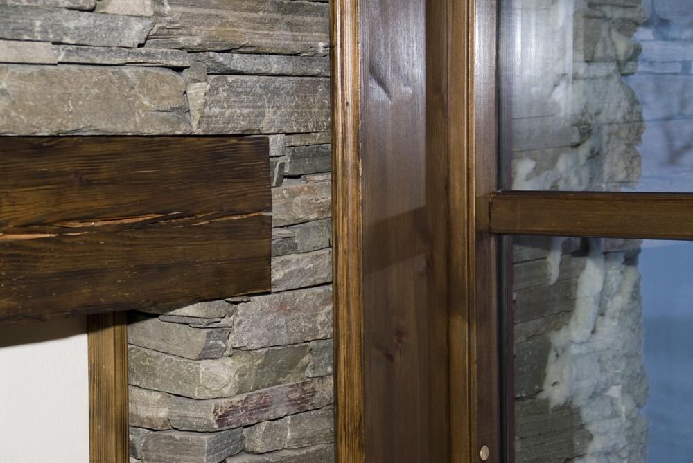 Gjennomgående vegg av tørrmur med innfelte hyller. Kuldebrobryter mellom vegg og vindu