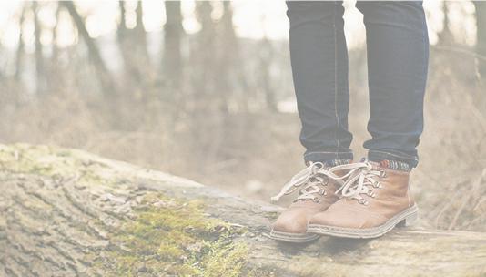 En person som står på en stokk i skogen.