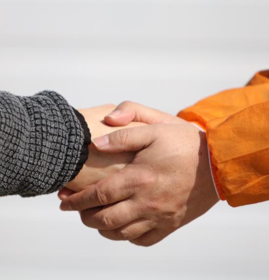 To hender som holder rundt en hånd
