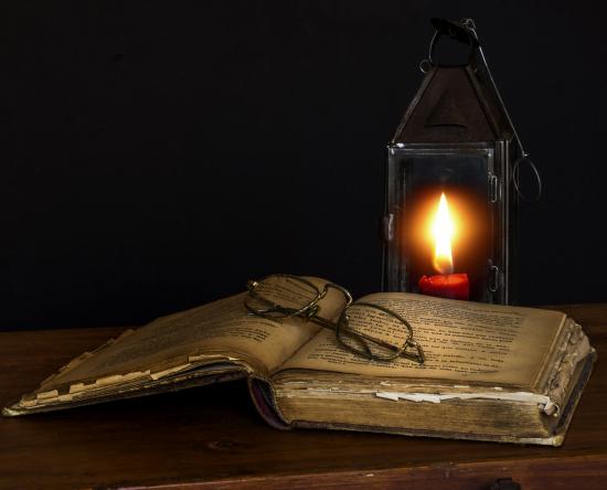 Bibel med briller oppå og stearinlys-lykt bak