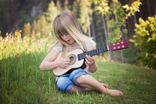 Et barn som øver på en gitar