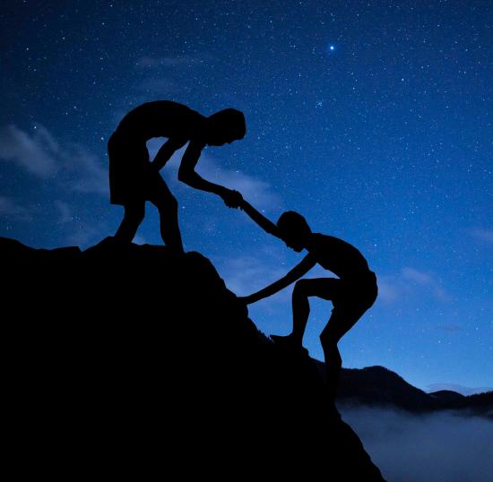 En person strekker ut en hånd for å hjelpe en annen opp en klippe