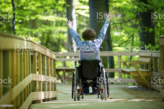 Mann i rullestol kjører på gangbro i natyren.