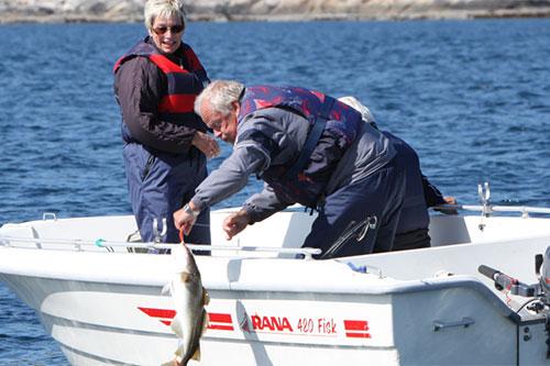 Mann og kvinne fisker fra båt