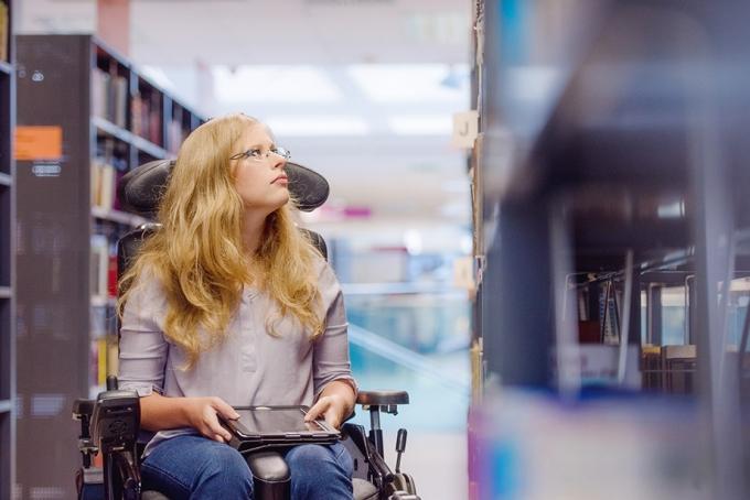 Ung kvinne i rullestol på bibliotek