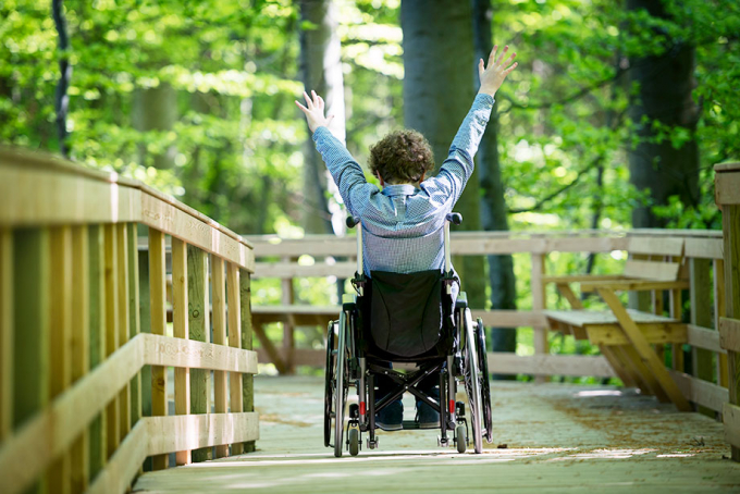 Mann i rullestol kjører på gangbro i naturen.