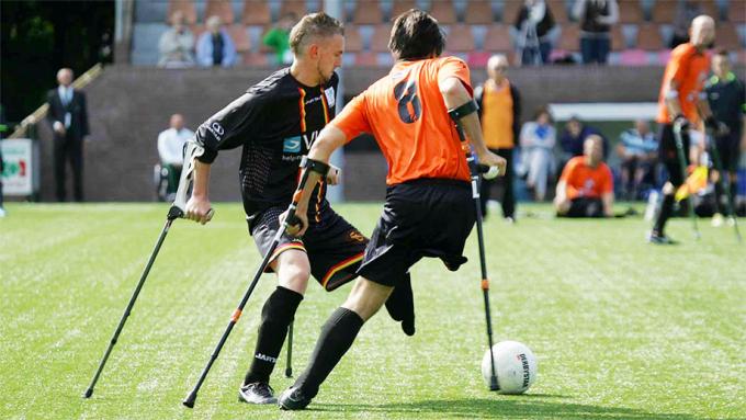 To menn spiller fotball. Begge har ett ben og bruker krykker i spillet.