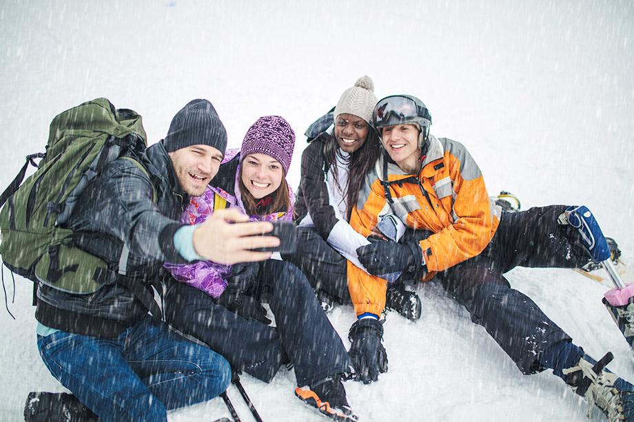 Fire unge turkledde mennesker tar selfie i snøen, den ene mannen har benprotese