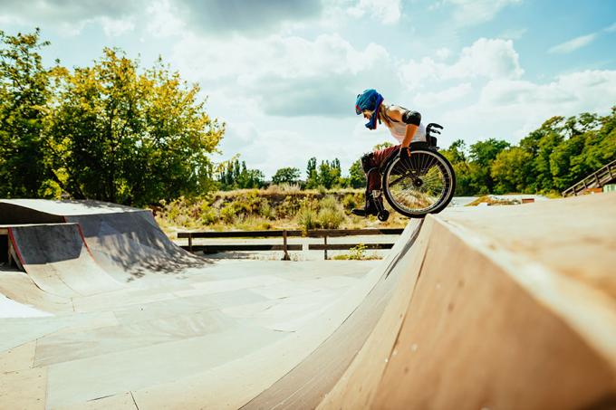 Ung kvinne i rullestol står på kanten av rampe i skatepark