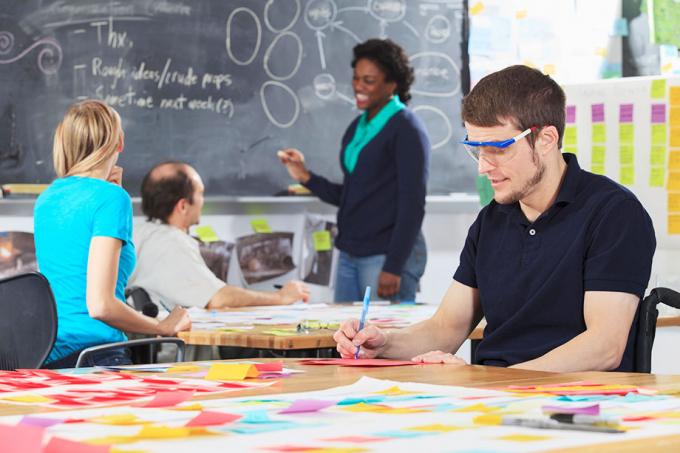 Mann i rullestol, iført vernebriller, sitter ved bord og jobber i et klasserom, med andre studenter og lærer i bakgrunnen.